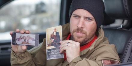 Jon Ritzheimer, 32, shows a family picture on his phone and a copy of the US Constitution to the media at  the Malheur National Wildlife Refuge Headquarters near Burns, Oregon,  January 4, 2016. The FBI on January 4 sought a peaceful end to the occupation by armed anti-government militia members at a US federal wildlife reserve in rural Oregon, as the standoff entered its third day. The loose-knit band of farmers, ranchers and survivalists -- whose action was sparked by the jailing of two ranchers for arson -- said they would not rule out violence if authorities stormed the site, although federal officials said they hope to avoid bloodshed. AFP PHOTO / ROB KERR / AFP / ROB KERR        (Photo credit should read ROB KERR/AFP/Getty Images)