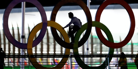 A man climbs on the Olympic rings near the basketball venue in the Olympic park on th eve before the opening ceremony of the 2016 Summer Olympics in Rio de Janeiro, Brazil, Thursday, Aug. 4, 2016. (AP Photo/Eric Gay)
