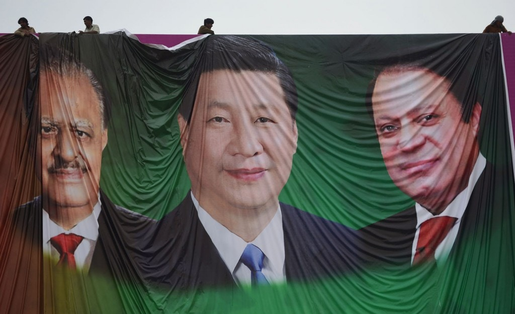 "Pakistani labourers arrange a welcoming billboard featuring pictures of visiting Chinese President Xi Jinping (C) and his Pakistani counterpart Mamnoon Hussain (L) and Prime Minister Nawaz Sharif (R) in Islamabad on April 18, 2015. Pakistan needs a ""huge amount of financing"" for infrastructure and energy projects and China is ready to announce help when President Xi Jinping visits next week, a foreign ministry official said April 17, 2015. AFP PHOTO / Farooq NAEEM        (Photo credit should read FAROOQ NAEEM/AFP/Getty Images)"