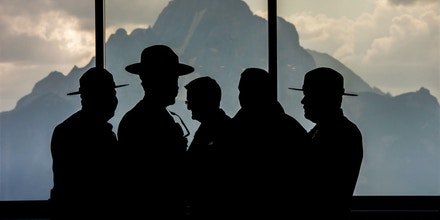 National Park Rangers stand silhouetted inside the lobby of Jackson Lake Lodge during the Jackson Hole economic symposium, sponsored by the Federal Reserve Bank of Kansas City, in Moran, Wyoming, U.S., on Thursday, Aug. 27, 2015. The symposium gathers central bankers, finance ministers, academics, and market participants to discuss the theme of