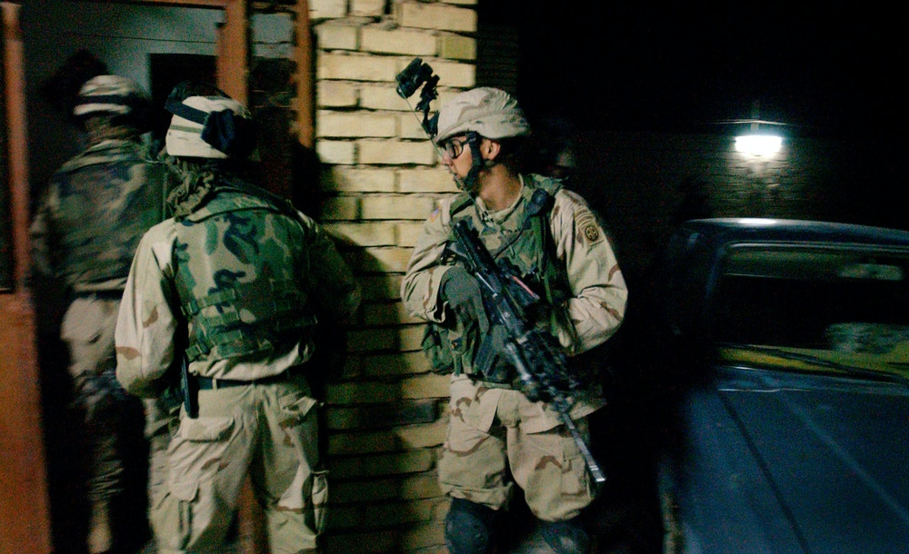 FALLUJAH, IRAQ - OCTOBER 31: U.S. Army soldiers from the 82nd Airborne 1st Battalion 505th Regiment sweep into a house during an October 31, 2003 cordon and search operation through three houses in the Iraqi town of Fallujah, Iraq. The raid yielded hidden rifles, rocket propelled grenade launchers and remote bomb detonation equipment in the houses and resulted in the detention of three individuals for questioning, including one believed to be a former Iraqi special forces soldier and explosives detonation expert.  (Photo by Scott Nelson/Getty Images)