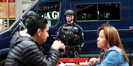 New York Police Department (NYPD) officers stand guard as a couple have their breakfast at the Times Square in New York, on May 17, 2016.   / AFP / Jewel SAMAD        (Photo credit should read JEWEL SAMAD/AFP/Getty Images)