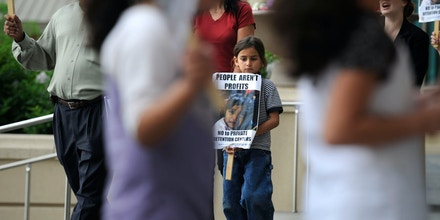 (HR) ABOVE: Itza Lasso-Karner 6 walks in the protest line holding a sign. He came with his father Harold Lasso, far left, to show their support for the protest. The Colorado Immigrant Rights Coalition (CIRC) was joined by Aurora residents, racial justice advocates and faith leaders in opposing the construction of a private detention center during a press conference at the Aurora Municipal Center. The protest and press conference took place prior to the Aurora City Council's vote on whether to hear the issue. At issue is the transnational corporation GEO Group's hopes to secure a contract with the U.S. Immigration and Customs Enforcement to build a 1,100 bed facility to be a immigration detention center. The group is protesting the poor care immigrants receive in immigrant detention centers the country. Helen H. Richardson/The Denver Post  (Photo By Helen H. Richardson/The Denver Post via Getty Images)