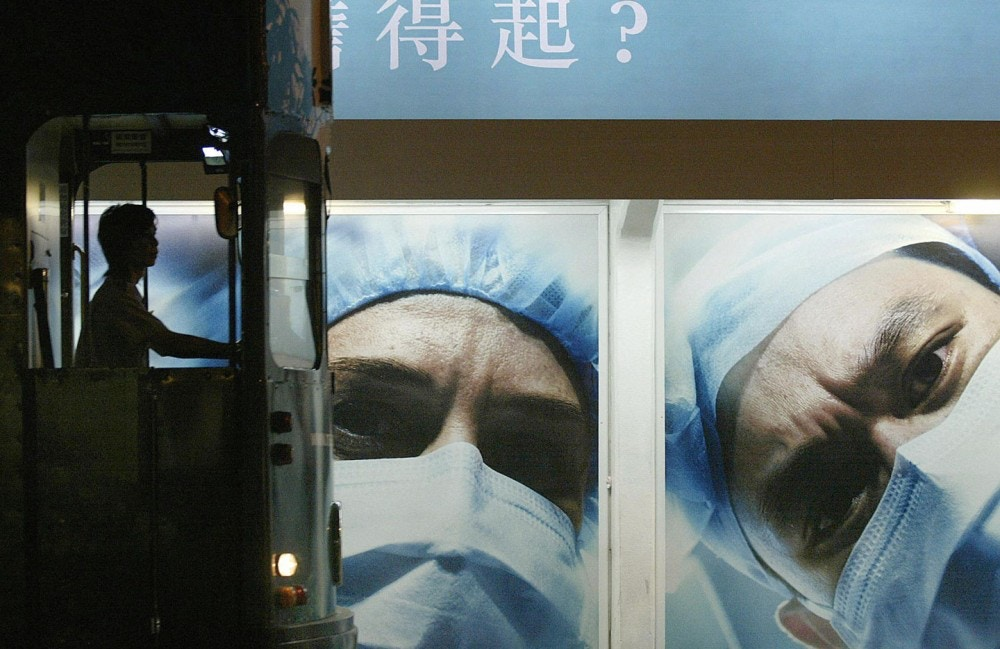 HONG KONG, CHINA:  A tram driver is silhouetted at a tram stop in front of a billboard showing medical workers doctor wearing masks to prevent the SARS disease in the Central district of Hong Kong, 07 May 2004.  Although China's first 2004 SARS patient, a lab worker in Beijing, will be discharged from hospital 10 May 2004 and only one person on the mainland has died so far, authorities in Hong Kong have continued to push public service advertisements warning local citizens to be diligent in the fight against the disease which caused almost 800 deaths in 2003, nearly 300 in the former British colony.    AFP PHOTO/Samantha SIN  (Photo credit should read SAMANTHA SIN/AFP/Getty Images)