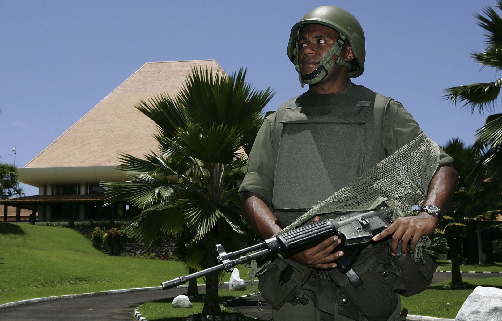 A Fijian military soldier stands guard on Parliament grounds.