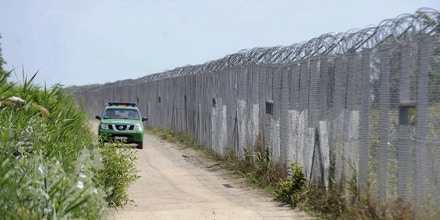 A Hungarian police vehicle patrols by the border fence between Hungary and Serbia near Asotthalom, Hungary, Tuesday, July 5, 2016. On this day Hungarian authorities introduced new border regulations, which are in line with the government's goal, to stem the uncontrolled inflow of illegal migrants. The new law aims to ensure that no one enters the country illegally but guarantees migrants an opportunity to submit asylum requests. Under the law, illegal entrants stopped within eight kilometres of the border will be escorted back over the border and offered an opportunity to apply for asylum at a transit zone. Migrants who comply with authorities, and apply for asylum, will not be expelled from the country and their appeals will be processed without delay. (Edvard Molnar/MTI via AP)