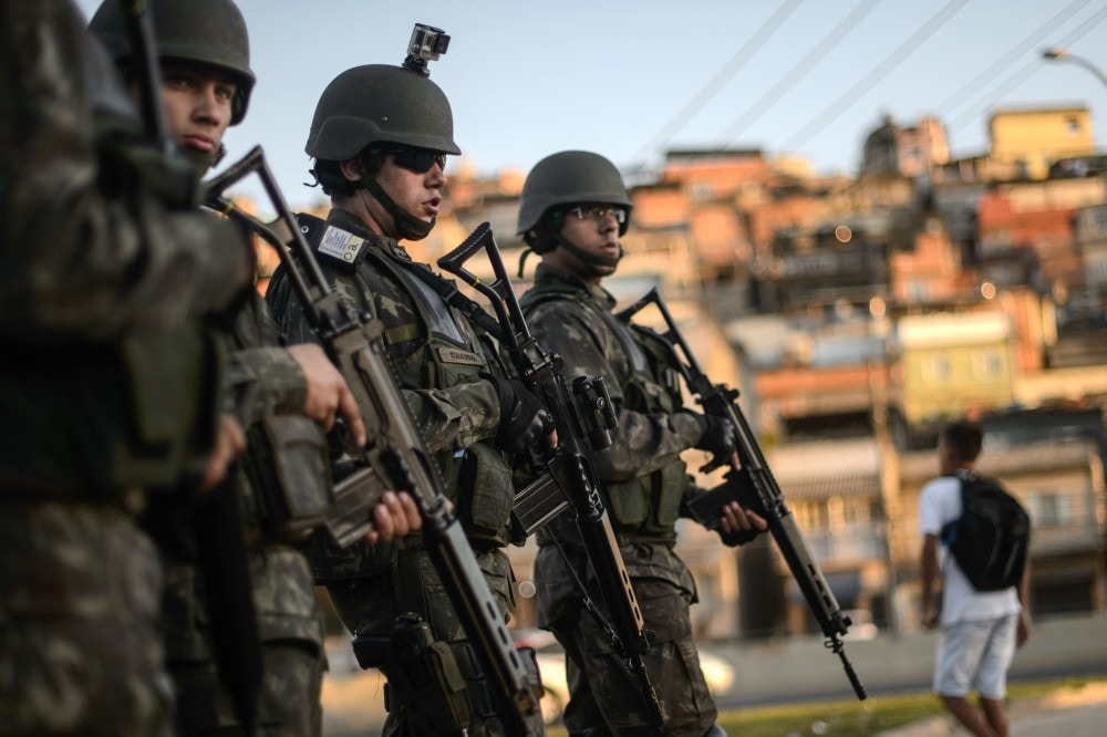Brazilian marines stand guard in the streets of the Mare favela complex for the last time before being completely relieved by the police, more than a year after being deployed to ramp up security in an area prone to gang warfare and drug trafficking ahead of last year's World Cup and South America's first ever Olympiad, in Rio de Janeiro, on June 30, 2015. In April, despite a recent upsurge in urban violence, Brazilian soldiers began to withdraw from the sprawling group of slums, handing back responsibility for law and order to military police who insist they will manage to pacify slum areas in the run-up to next year's Olympics.  AFP PHOTO / CHRISTOPHE SIMON        (Photo credit should read CHRISTOPHE SIMON/AFP/Getty Images)