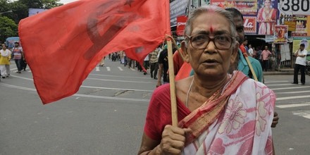 A supporter of Communist Party of India-Marxist (CPIM) walks with party flag as she joins with others during a nationwide strike, in Kolkata, India, Friday, Sept. 2, 2016. The strike was called against allegedly government's anti labor policies and demanded higher minimum wages and provision of social security to unorganized workers. (AP Photo/Bikas Das)