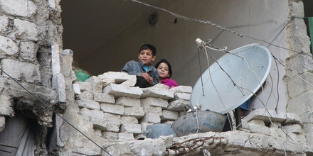 In this Feb. 11, 2016, file photo, children peer from a partially destroyed home in Aleppo, Syria. After four years of grinding battles, Aleppo's divided residents face a common fear as the prospect of a total siege looms. Syria's largest city used to be its economic locomotive, now it is has become an emblem of its stalemated civil war. (Alexander Kots/Komsomolskaya Pravda via AP, File)