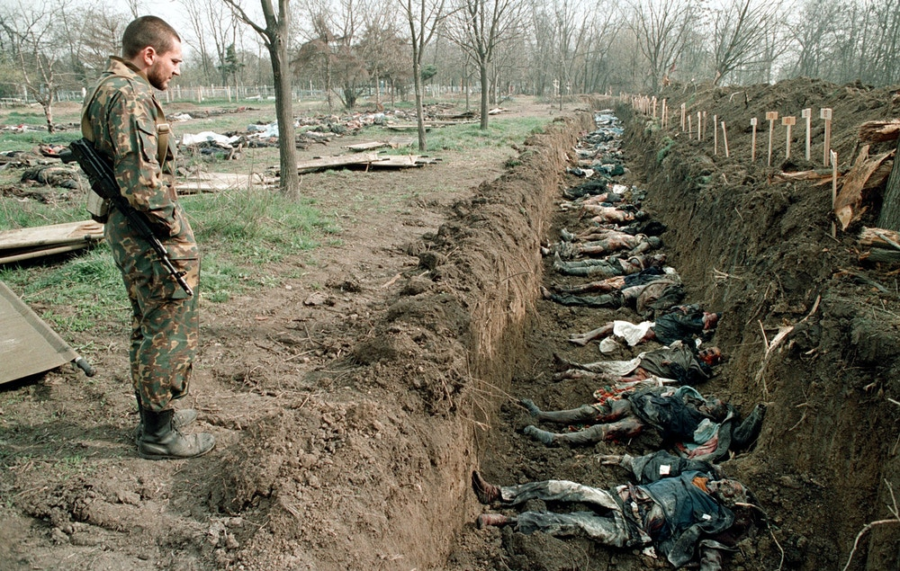 Russian Army soldier inspects 31 March 1995 at a cemetery in Grozny, capital of the breakaway southern republic of Chechnya, the bodies of Chechen civilians killed during the winter fights and exhumed for identification. Russian troops entered Chechnya 11 December 1994 with the stated aim of introducing constitutional rule in the Caucasus republic. Russian forces fought a brutal war in 1994-1996 to crush separatist rebels in Chechnya that ended in defeat for Moscow and killed 80,000 people. AFP PHOTO ALEXANDER NEMENOV         (Photo credit should read ALEXANDER NEMENOV/AFP/Getty Images)