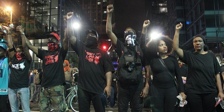 Protesters raise their fists during a peaceful march through the streets of Charlotte, North Carolina on September 22, 2016.