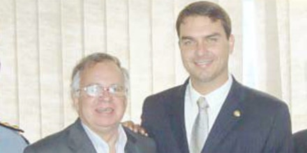 From left, Pedro Chavarry Duarte and Flavio Bolsonaro pose for a photo published in a 2012 newsletter of an association of retired police officials reporting on an event they attended together.