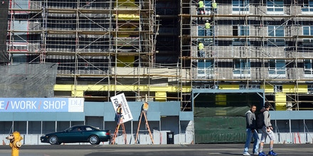 Pedestrians cross the street as construction workers work on the exterior of a commercial and residential building going up in Hollywood, California on January 22, 2014.  US housing starts dived almost 10 percent in December from a five-year high but maintained robust growth for the year as the housing market recovers,  government data showed last week, as new residential construction fell to a seasonally adjusted annual rate of 999,900 in December. The full year 2013 data underlined the strength of last year's housing market recovery following the 2006 collapse of a price bubble. AFP PHOTO/Frederic J. BROWN        (Photo credit should read FREDERIC J. BROWN/AFP/Getty Images)
