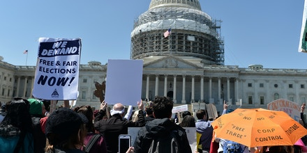 Protesters hold up signs during a Democracy Spring demonstration in Washington, DC on April 13, 2016, calling for changes in voting laws and campaign finance.