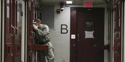 GUANTANAMO BAY, CUBA - JUNE 26:  (EDITORS NOTE: Image has been reviewed by the U.S. Military prior to transmission.) A U.S. Army Military Police checks in on a detainee during morning prayer at Camp V in the U.S. military prison for 'enemy combatants' on June 26, 2013 in Guantanamo Bay, Cuba. President Barack Obama has recently spoken again about closing the prison which has been used to hold prisoners from the invasion of Afghanistan and the war on terror since early 2002.  (Photo by Joe Raedle/Getty Images)