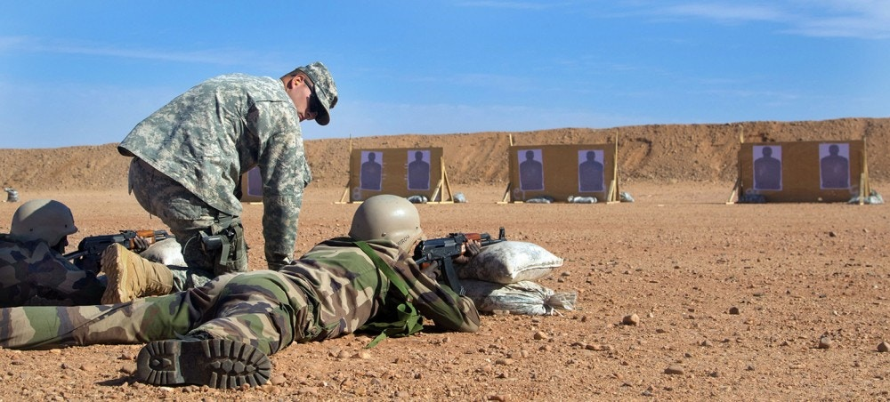A U.S. Army trainer coaches a Republic of Niger soldier on marksmanship techniques at an AK-47 qualification range near Agadez, Niger. (U.S. Army Africa photo by Spc. Craig Philbrick)
