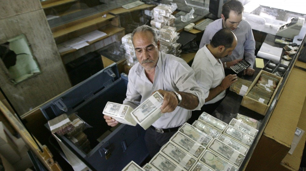 TO GO WITH AFP STORY BY SAMMY KETZA banker stacks packed Syrian lira bills at the Central Bank in Damascus on August 25, 2011. US sanctions have forced Syria to stop all transactions in US dollars, with the country turning completely to euro deals, the governor of the Central Bank Adib Mayaleh told the AFP during an interview. AFP PHOTO/JOSEPH EID (Photo credit should read JOSEPH EID/AFP/Getty Images)