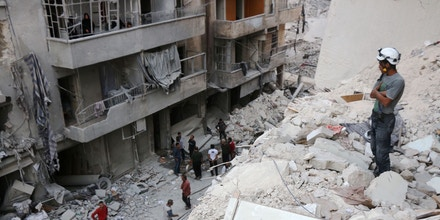 A Syrian civil defence volunteer, known as the White Helmets, stands on the rubble of destroyed buildings during a rescue operation following a government forces air strike on the rebel-held neighbourhood of Bustan al-Basha in the northern city of Aleppo, on October 4, 2016.Assad's forces advanced on rebels during intense street fighting in the opposition-held east of Aleppo city, which Russia has been accused of bombing indiscriminately including targeting its hospitals. / AFP / THAER MOHAMMED (Photo credit should read THAER MOHAMMED/AFP/Getty Images)