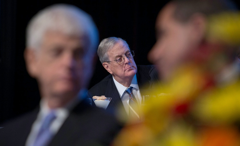 "David Koch, executive vice president of chemical technology for Koch Industries Inc., center, listens as Ben S. Bernanke, chairman of the U.S. Federal Reserve, unseen, speaks to the Economic Club of New York in New York, U.S., on Tuesday, Nov. 20, 2012. Bernanke said that an agreement on ways to reduce long-term federal budget deficits could remove an impediment to growth, while failure to avoid the so-called fiscal cliff would pose a ""substantial threat"" to the recovery. Photographer: Scott Eells/Bloomberg via Getty Images"