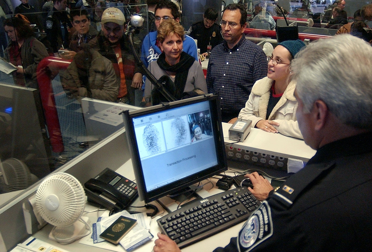 Carolina Velasco Cedeno, second from right, looks up toward a mini camera as U.S. Customs and Border Protection officer Roberto Alvarado, right front, records her picture and finger prints as Cedeno's parents, Carmen Cedeno de Velasco, center left, and Carlos Velasco Virgin, center right, look on upon their arrival at Dallas Fort Worth International Airport from Guadalajara, Mexico, Monday, Jan. 5, 2004, in Grapevine, Texas. In the background are other visitors waiting to be processed by other officers. (AP Photo/Tony Gutierrez)