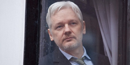 WikiLeaks founder Julian Assange is seen through the window of the door leading to the balcony of the Ecuadorian embassy in central London on February 5, 2016 from where he addressed the media.During a press conference on February 5 Julian Assange, speaking via video-link, called for Britain and Sweden to