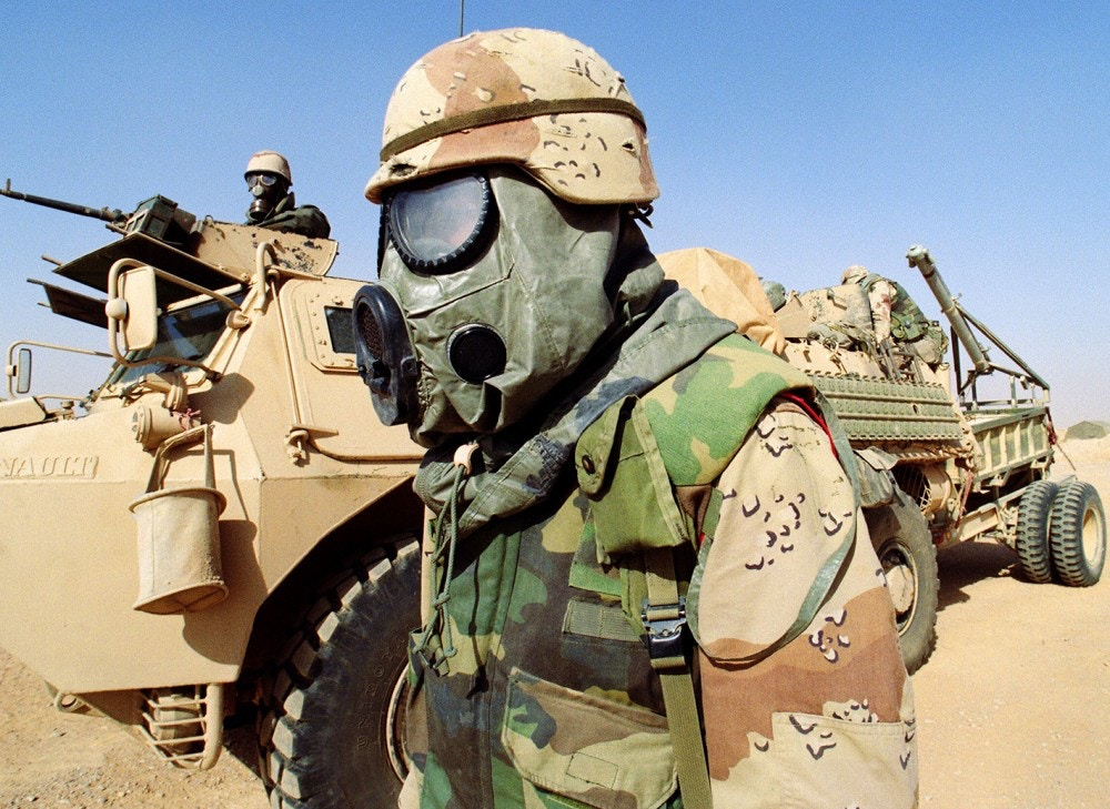 "A US soldier (C) stands 09 February 1991 somewhere in Saudi Arabian desert in front of a French armored vehicle (VAB) from the 6th Foreign Legion Engineers Regiment. Both soldiers are wearing chemical warfare equipment. Iraq's invasion of Kuwait 02 August 1990, ostensibly over violations of the Iraqi border, led to the Gulf War which began 16 January 1991. A U.S.-led multinational force expelled Iraq from Kuwait during the ""Desert Storm"" offensive and a cease-fire was signed 28 February 1991.   (Photo credit should read MICHEL GANGNE/AFP/Getty Images)"