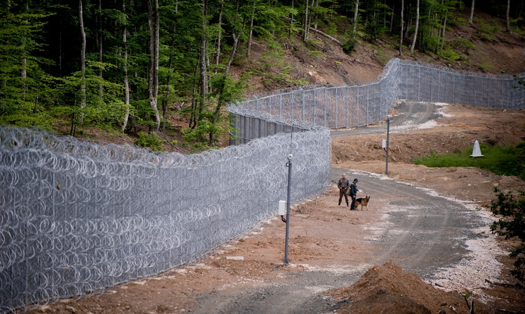 Bulgarian border police personal stand next to a barbed wire fence at the border between Bulgaria and Turkey near the Bulgarian town of Malko Tarnovo on May 22, 2016. / AFP / NIKOLAY DOYCHINOV        (Photo credit should read NIKOLAY DOYCHINOV/AFP/Getty Images)