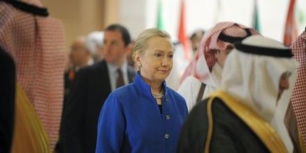 US Secretary of State Hillary Clinton (C) is escorted by Saudi protocol staff and security as she arrives for a group picture with her Gulf counetrparts during their meeting in the Saudi capital of Riyadh, on March 31, 2012.  Clinton was to speak about plans for a Gulf missile shield against Iran and ways to press Tehran's ally Syria to stop killing Syrians.     AFP PHOTO/FAYEZ NURELDINE-POOL (Photo credit should read FAYEZ NURELDINE/AFP/Getty Images)