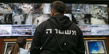People observe surveillance cameras on screens inside the Jerusalem Police's Mabat 2000 unit.