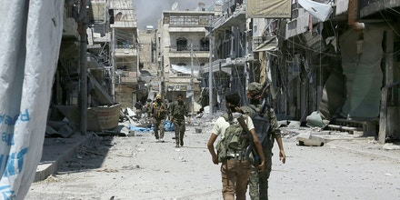 Members of the Syrian Democratic Forces (SDF) patrol a street in the northern Syrian town of Manbij on August 7, 2016, as they comb the city in search of the last remaining jihadists, a day after they retook it from the Islamic State group.A coalition of Arab and Kurd fighters on August 6, 2016 seized the Islamic State (IS) group stronghold of Manbij, two months after launching an operation to capture the strategic city in northern Syria, a monitor said. The town had served as a key transit point along IS's supply route from the Turkish border to Raqa, the de facto capital of its self-styled Islamic