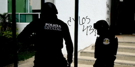 Police officers stand near graffiti painted during protests by students from the Raul Isidro Burgos teacher training college in Ayotzinapa on the walls of the palace of justice building in Iguala, Guerrero state, Mexico on September 22, 2016. Demonstrations have broken out ahead of September 26, 2016, the second anniversary of the disappearance of 43 teacher training college students in Ayotzinapa. / AFP / ALFREDO ESTRELLA (Photo credit should read ALFREDO ESTRELLA/AFP/Getty Images)