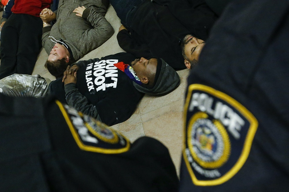 New York Police Department officers watch demonstrator as they lie down on the floor of Gran Central Station in New York on December 6, 2014, as part of a die-in. Protesters in many US cities are demonstrating against the recent decisions by grand juries in New York and Ferguson, Missouri, not to charge police officers involved in the deaths of two African-American men.  AFP PHOTO/Eduardo Munoz Alvarez        (Photo credit should read EDUARDO MUNOZ ALVAREZ/AFP/Getty Images)