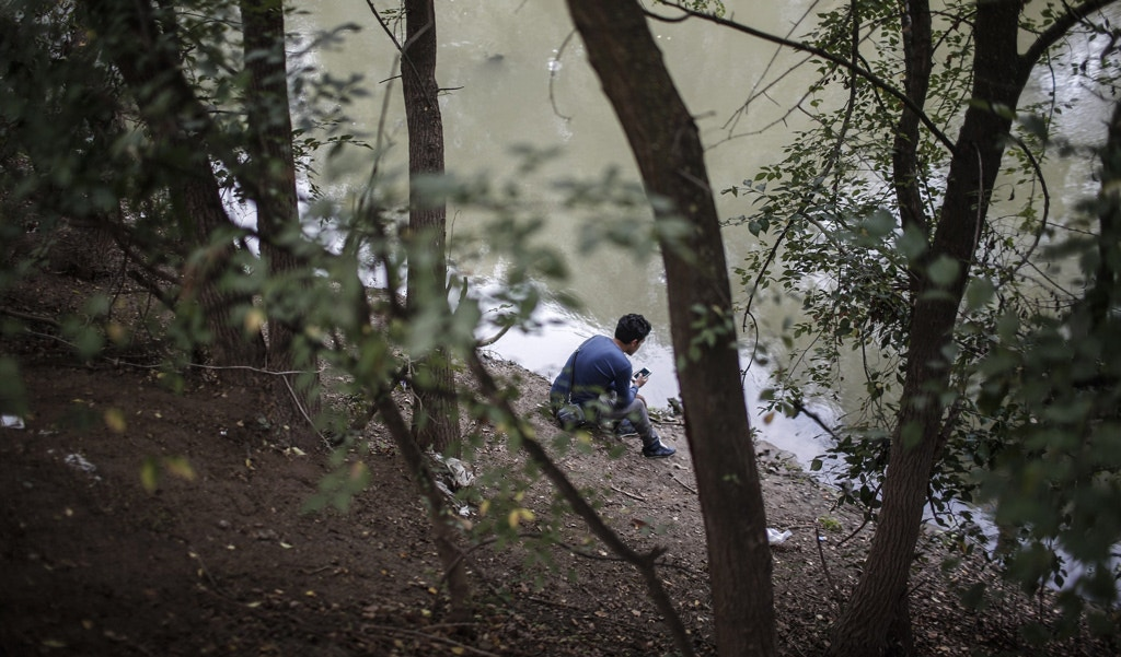 A refugee man sits near the river while waiting to cross to Europe near Turkeys western border with Greece and Bulgaria, in Edirne, on September, 23, 2015. Hundreds of migrants have made the trek to Edirne in the hope of being allowed to cross into neighboring Greece or Bulgaria and avoid the often-risky journey across the Aegean Sea. Many arrived last week but have been blocked from approaching the border by law enforcement. AFP PHOTO/STR        (Photo credit should read STR/AFP/Getty Images)