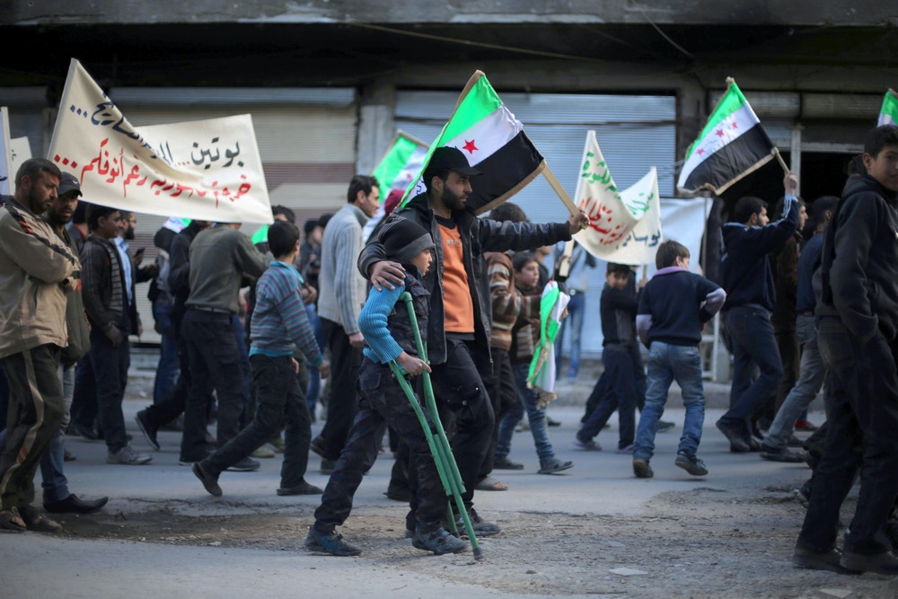 Protesters hold flags and placards during an anti-regime demonstration in the rebel-held town of Saqba, on the outskirts of the Syrian capital Damascus, on March 16, 2016.Syria's war is entering its sixth year with a glimmer of hope that a landmark ceasefire and a push for peace could help resolve a conflict that has sent hundreds of thousands fleeing to Europe. / AFP / AMER ALMOHIBANY        (Photo credit should read AMER ALMOHIBANY/AFP/Getty Images)