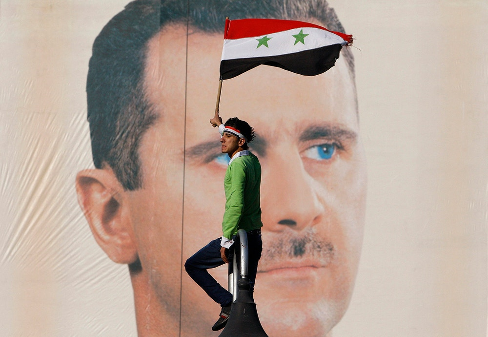 "FILE - A pro-Syrian regime protester waves a Syrian flag as he stands in front of portrait of Syrian President Bashar Assad, during a protest against sanctions, Damascus, Syria, in this Dec. 2, 2011 file photo. Speaking to ABC's Barbara Walters in a rare interview that aired Wednesday, Dec. 7, 2011 President Bashar Assad maintained he did not give a command ""to kill or be brutal.""  (AP Photo/Muzaffar Salman, File)"