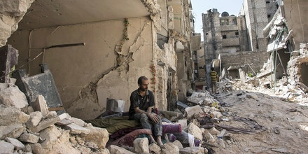 A Syrian man sits in the rubble following a barrel bomb attack the previous day in Aleppo, Syria on September 17, 2015.