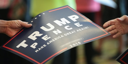 A volunteer hands out signs before the start of a campaign rally with Republican presidential nominee Donald Trump at the KI Convention Center on Oct. 17, 2016, in Green Bay, Wisconsin.