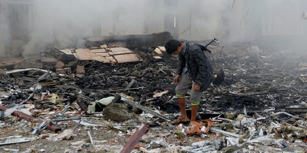 A Yemeni inspects the rubble of a destroyed building following an air strike on a funeral ceremony in the capital Sanaa on October 8, 2016.Rebels in control of Yemen's capital accused the Saudi-led coalition fighting them of killing or wounding dozens of people in air strikes on Sanaa. The insurgent-controlled news site sabanews.net said that coalition planes hit a building in the capital where people had gathered to mourn the death of an official, resulting in
