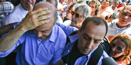 Brazil's presidential candidate Jose Serra (L) of the Social Democratic Party of Brazil protects his head after being