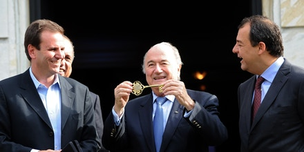 FIFA's President Joseph S. Blatter (C) shows the Rio de Janeiro City key next to Rio de Janeiro's Major Eduardo Paes (L) and Rio de Janeiro's Governor Sergio Cabral at the City Palace in Rio de Janeiro, Brazil, on July 29, 2011. Blatter is in Rio de Janeiro to take part in the Preliminary draw for the FIFA World Cup 2014 which will be held on Saturday. AFP PHOTO/Evaristo SA (Photo credit should read EVARISTO SA/AFP/Getty Images)