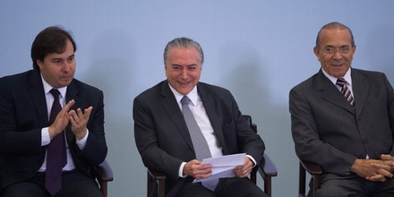 Brazilian President Michel Temer (C), Lower House President Rodrigo Maia and Chief of Staff Eliseu Padilha (R) attend a ceremony to promote new economy laws at Plantalto palace on October 27, 2016.Temer, who took over after the impeachment of Dilma Rousseff in August, urged an oil and gas conference in Rio de Janeiro to join what he said was an economy on the mend. / AFP / ANDRESSA ANHOLETE (Photo credit should read ANDRESSA ANHOLETE/AFP/Getty Images)