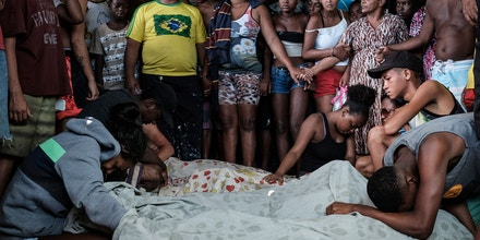 Family members mourn victims from a police operation against drug dealers that occurred on November 19 at Cidade de Deus favela (community) in Rio de Janeiro, Brazil, on November 20, 2016.Rio, which is home to 6.5 million people and drastic social inequality, suffers from high levels of criminality, made worse by heavily armed gangs of narcotraffickers, but also by the presence of paramilitary militias. / AFP / YASUYOSHI CHIBA (Photo credit should read YASUYOSHI CHIBA/AFP/Getty Images)