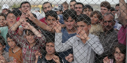 Migrants stand behind a fence at the Nizip refugee camp in Gaziantep province, southeastern Turkey, Saturday, April 23, 2016. German Chancellor Angela Merkel and top European Union officials, under pressure to reassess a migrant deportation deal with Turkey, are traveling close to Turkey's border with Syria on Saturday in a bid to bolster the troubled agreement.   (AP Photo/Lefteris Pitarakis)