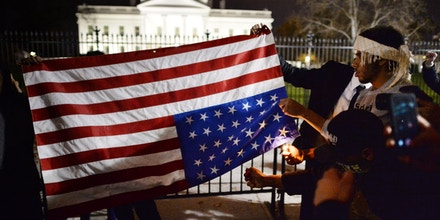 Protesters try unsuccessfully to burn an upside down US flag during a protest outside the White House in Washington, DC on November 25, 2014, one day after a grand jury decision not to prosecute a white police officer for the killing of an unarmed black teen in Ferguson, Missouri. AFP PHOTO/MLADEN ANTONOV        (Photo credit should read MLADEN ANTONOV/AFP/Getty Images)