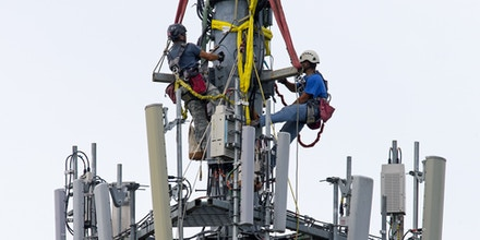 Telecom workers are suspended from a crane as they make additions to an existing cellphone tower along Interstate 66 in Vienna, Virginia, on June 22, 2016.