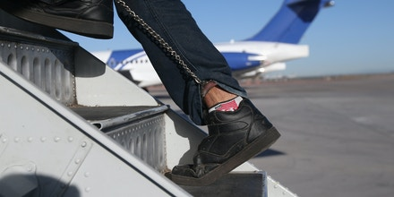 MESA, AZ - FEBRUARY 28: A Honduran immigration detainee, his feet shackled and shoes laceless as a security precaution, boards a deportation flight to San Pedro Sula, Honduras on February 28, 2013 in Mesa, Arizona. U.S. Immigration and Customs Enforcement (ICE), operates 4-5 flights per week from Mesa to Central America, deporting hundreds of undocumented immigrants detained in western states of the U.S. With the possibility of federal budget sequestration, ICE released 303 immigration detainees in the last week from detention centers throughout Arizona. More than 2,000 immigration detainees remain in ICE custody in the state. Most detainees typically remain in custody for several weeks before they are deported to their home country, while others remain for longer periods while their immigration cases work through the courts. (Photo by John Moore/Getty Images)