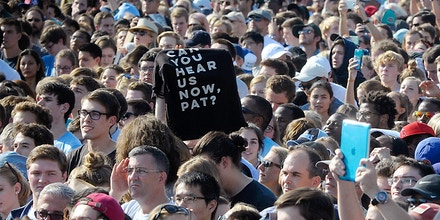 Someone in the crowds holds up a T-Shirt reading