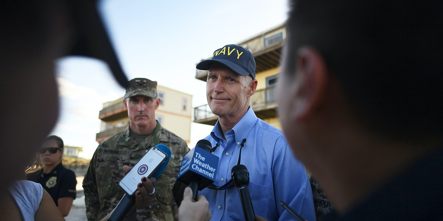 Florida governor Rick Scott (C) speaks to the meida as he visits a damaged beach in St Augustine, Florida, on October 8, 2016, after Hurricane Matthew passed the area.Hurricane Matthew weakened to a Category 1 storm Saturday as it neared the end of a four-day rampage that left a trail of death and destruction across the Caribbean and up the US Atlantic coast. The full scale of the devastation in hurricane-hit rural Haiti became clear as the death toll surged past 400, three days after Hurricane Matthew leveled huge swaths of the country's south. / AFP / Jewel SAMAD (Photo credit should read JEWEL SAMAD/AFP/Getty Images)