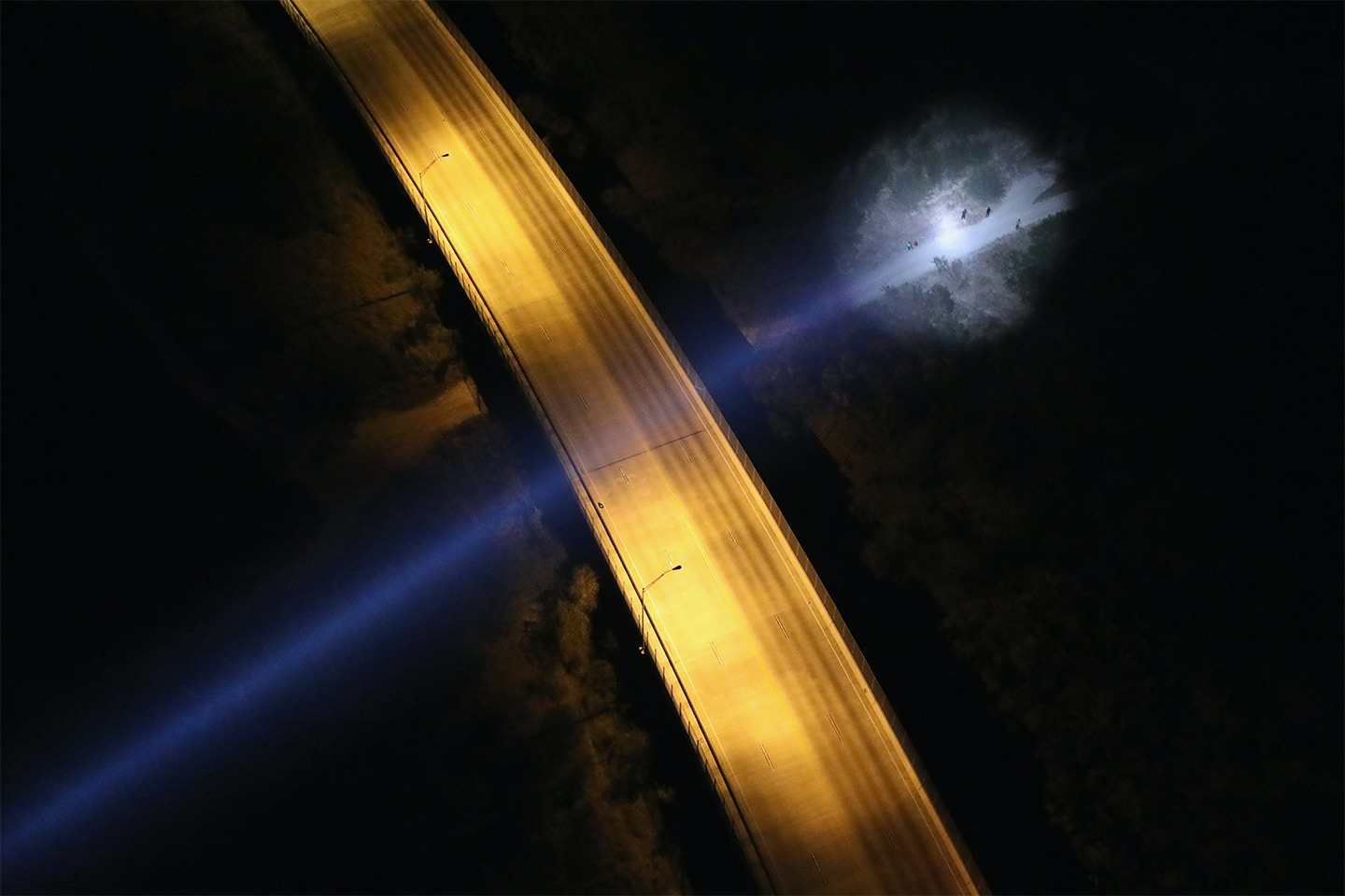 MCALLEN, TX - OCTOBER 18:  A spotlight from a U.S. Customs and Border Protection helicopter shines on women and children seeking asylum on October 18, 2016 in McAllen, Texas. U.S. Air and Marine Operations agents fly over border areas, coordinating with Border Patrol agents on the ground to stop undocumented immigrants and drug smugglers from entering the U.S. Immigration and border security have become major issues in the American Presidential campaign.  (Photo by John Moore/Getty Images)