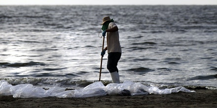 A worker hired by BP to help clean the beaches of oil work in a contaminated area on June 12, 2010 in Grand Isle, Louisiana.